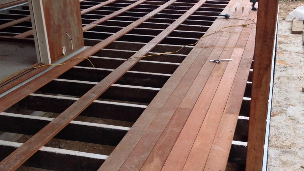 A picture of hardwood decking being laid on hardwood joists