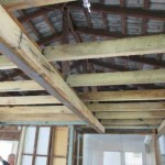 Pitched roof framing exposed to show ceiling joists, rafters, roof battens and roof tiles.